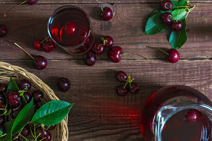 cold cherry juice in a glass and pitcher with cherries inside on wooden table with ripe berries in wicker basket. top view