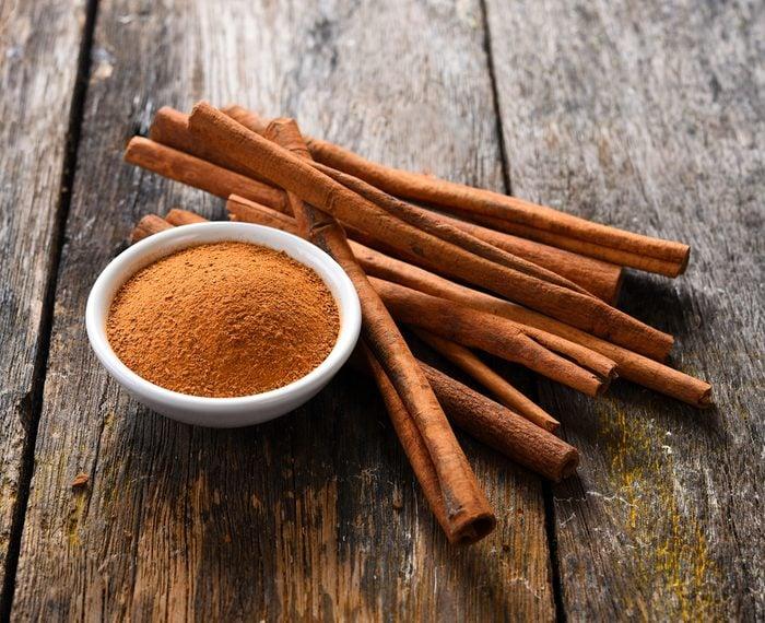 Cinnamon sticks and cinnamon powder on wood