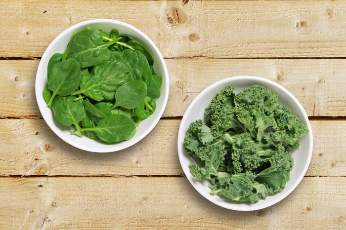 Two white bowls one containing spinach leaves and one containing chopped kale leaves. Shot from above on a rustic wooden background