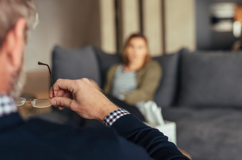 Hands of psychologist holding glasses and listening to woman during therapy session