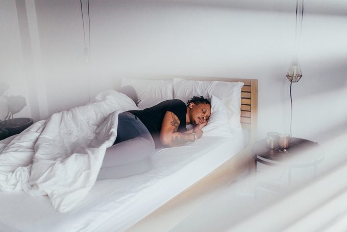 African man sleeping in bedroom with woman at back. Couple sleeping back to back on bed.