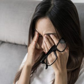 Young woman rubbing her eyes feel painful and take off her glasses siiting on sofa and rest one's eyes at home