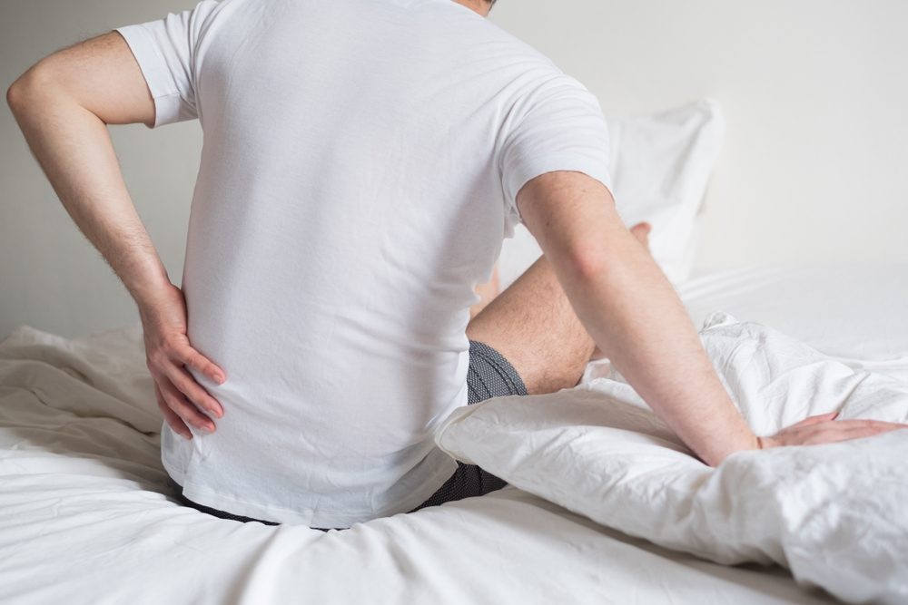 Rear view of one man sitting on bed having back pain