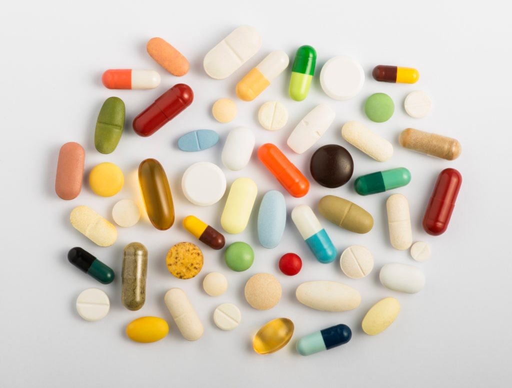 vitamins and supplements pills overhead studio gray background