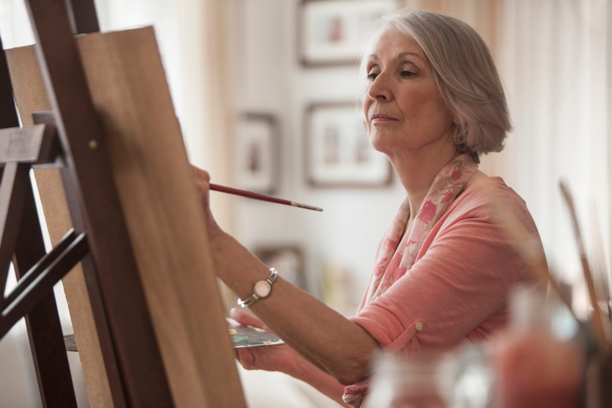 senior woman painting on canvas