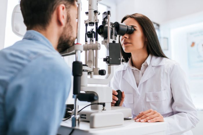 Female ophthalmologist is checking the eye vision of young man in modern clinic.