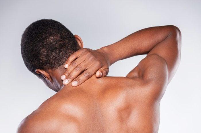 Young shirtless man touching his neck.
