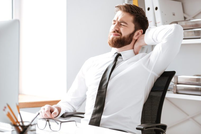 Young businessman sitting in office while stretching.