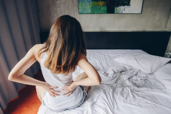 Young woman sitting on the bed holding her back with a backache.