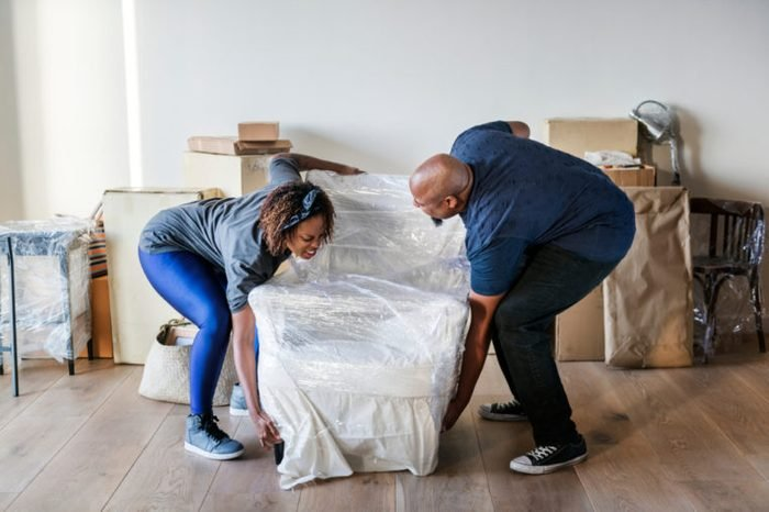 Couple moving furniture into a new house.