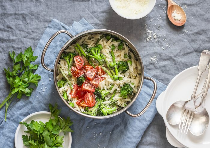 One pot orzo primavera. Orzo pasta with asparagus, broccoli, green peas and cream in a saucepan. On a light background, top view