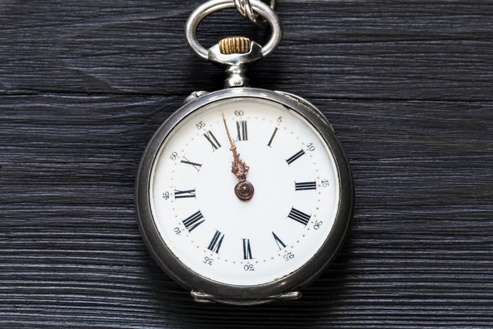 two minutes to twelve o'clock on vintage pocket watch on black wooden background