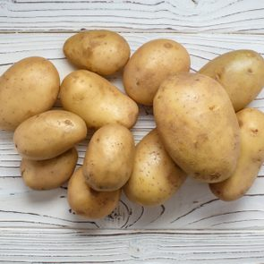 Young potatoes on white wooden background, view from above