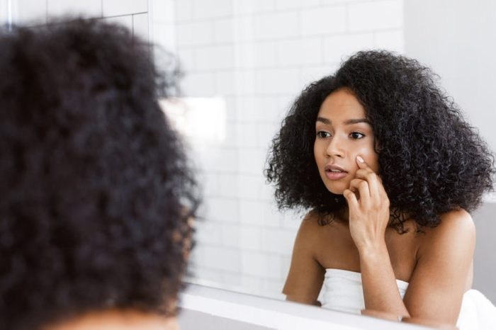 Young woman looking at mirror and examining her skin