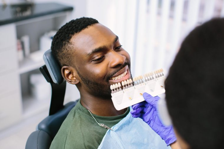 dentist holding up veneers to man's mouth