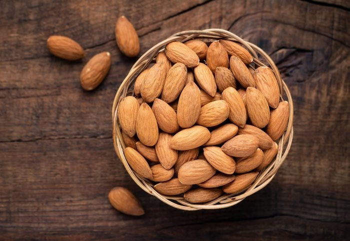 Almonds in willow bowl against dark rustic wooden background. Overhead view