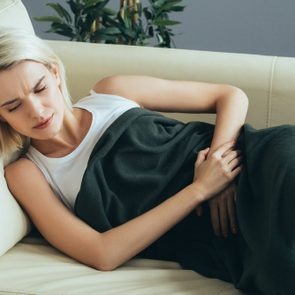 Womsn stomach pain. Female portrait painful girl on sofa bed at home