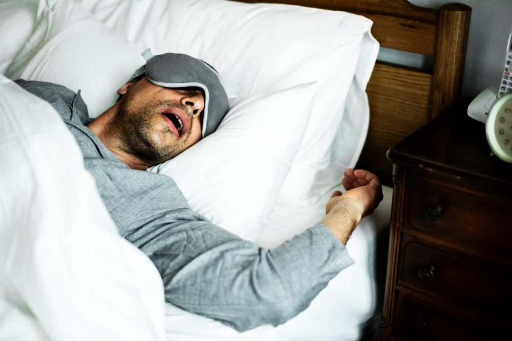 A man sleeping on a bed with sleep mask on