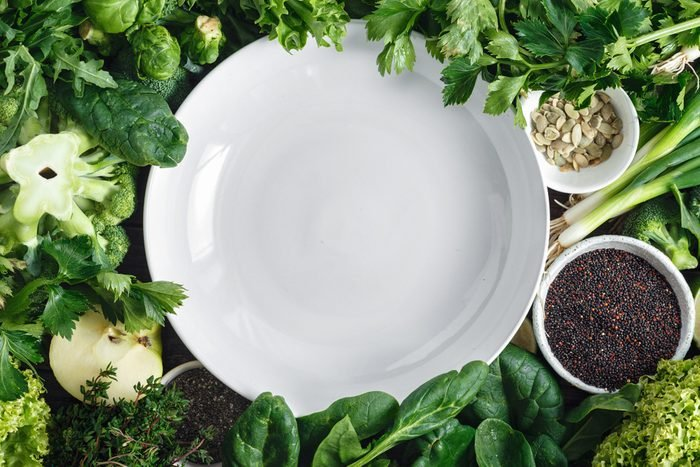 plate surrounded by green vegetables and seeds