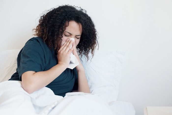 woman in bed, blowing her nose