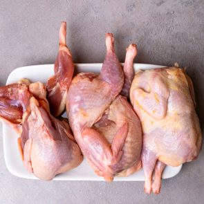 Fresh quails meat prepared to baking on grey background
