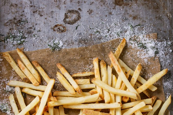 Fast food french fries potatoes with skin served with salt and herbs on baking paper over old rusty metal background. Top view, space for text