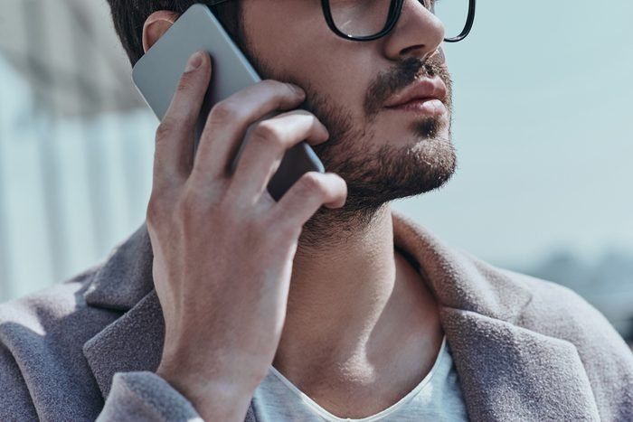 On the phone. Close-up of young modern man talking on the smart phone while standing outdoors
