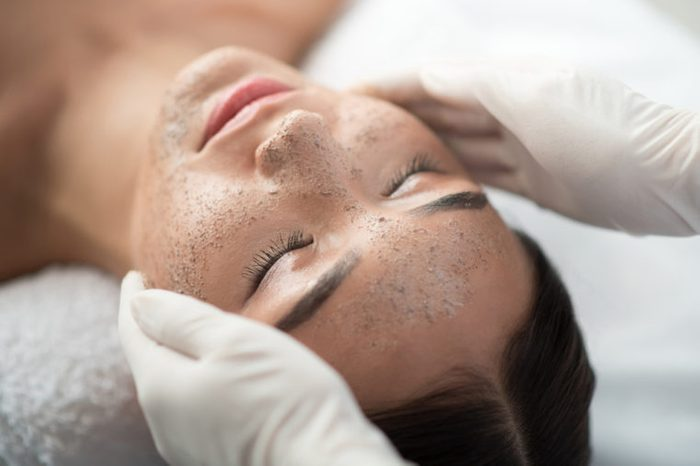 Close up of young woman getting facial skin treatment at spa. Cosmetician hands applying peeling mask on her face