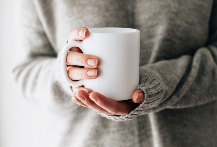 Closeup of female hands with a mug of beverage. Beautiful girl in grey sweater holding cup of tea or coffee in the morning sunlight. Mug for your design. Empty.