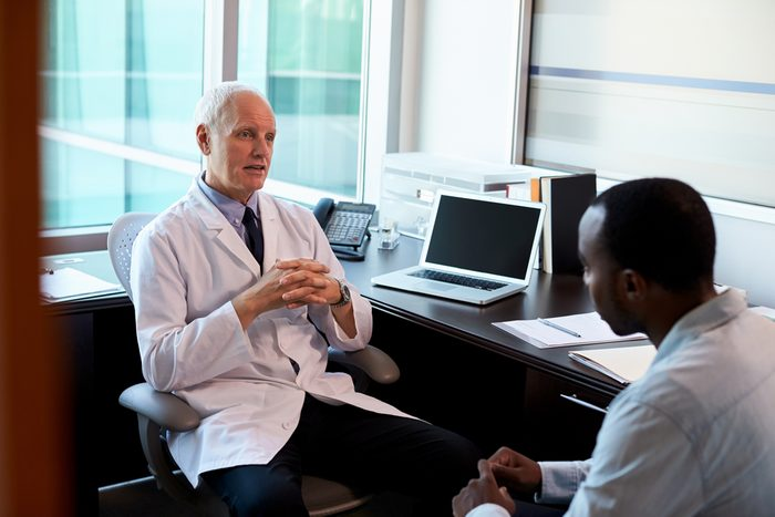 Doctor In Consultation With Male Patient In Office