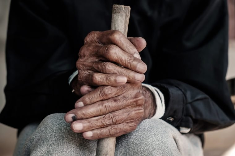 hand of a old man begging for money because of the hunger holding a cane.vintage tone