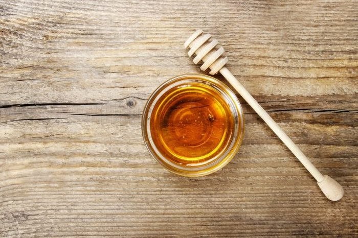 Bowl of honey on wooden table. Symbol of healthy living and natural medicine. Aromatic and tasty. Top view.
