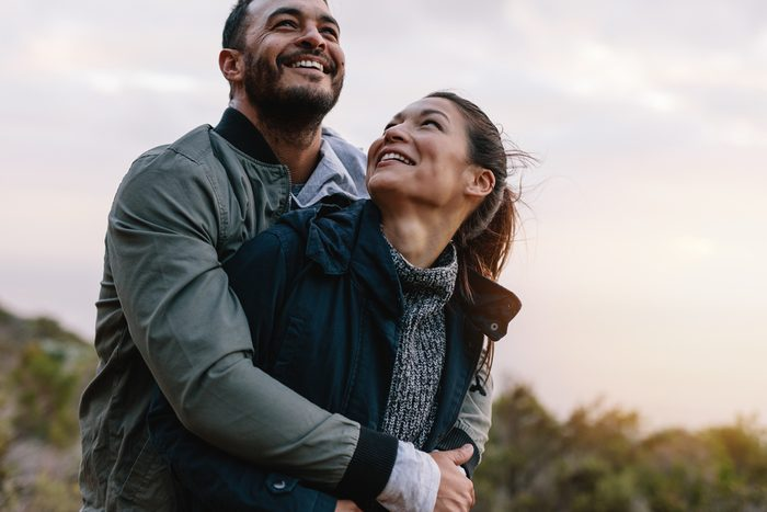 Romantic young couple embracing in nature. Happy young man and woman on vacation in countryside.