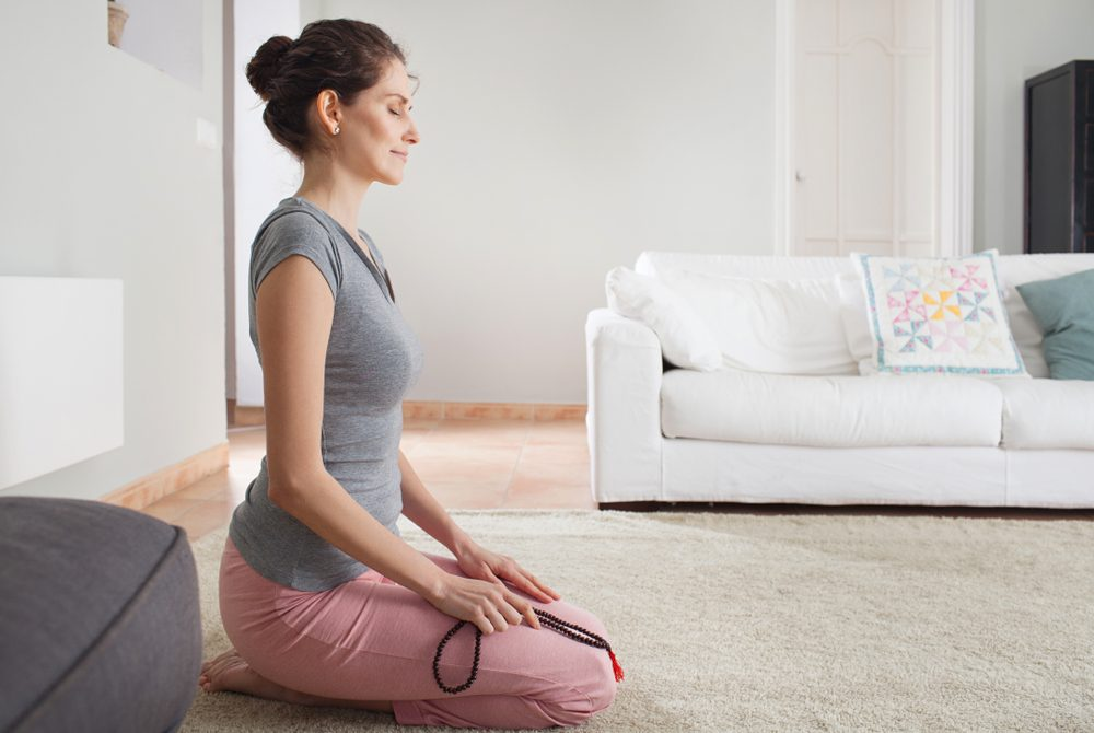Side view of middle aged woman kneeling on carpet doing yoga with beads collar, home living room interior. Healthy female meditating, mind wellness mindful sport, indoors. Recreation lifestyle.