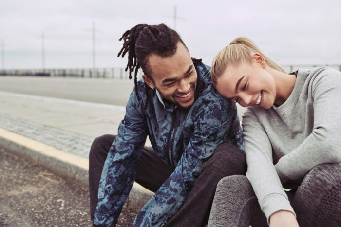 Laughing young couple sitting on a road together taking a break from a run on an overcast day