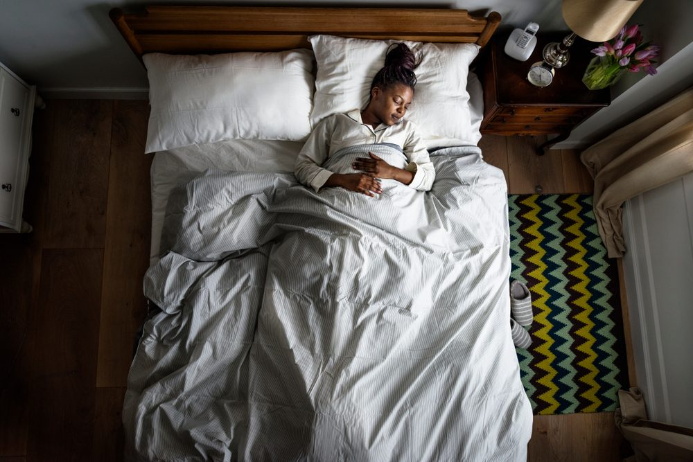 Afrikaans-Amerikaanse vrouw op bed die slaapt