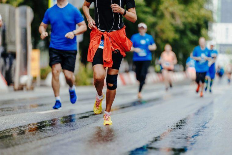 female athlete with knee pad running marathon on wet road