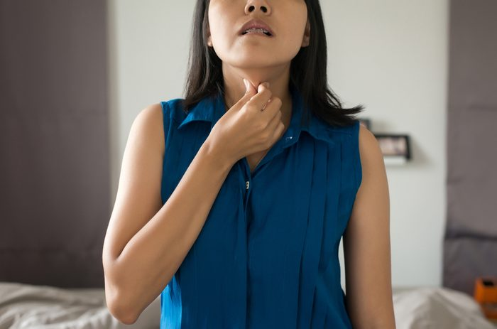 Woman have a sore throat,Female touching neck with hand,Healthcare Concepts