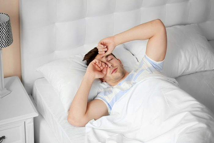 Young man rubbing his eyes in the morning