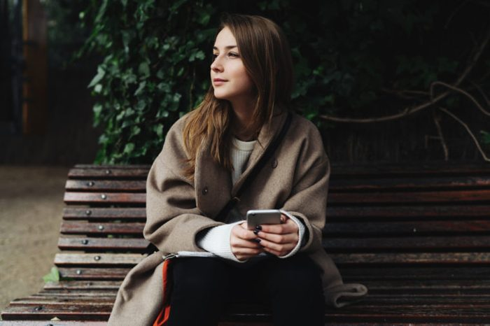 Hipster girl with her phone on a park bench