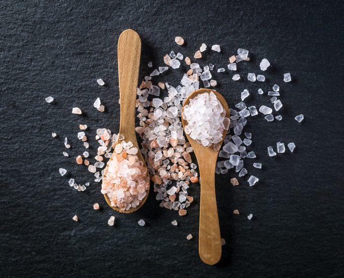 Two wooden spoons with pink himalayan and white kithchen salt on dark stone background. Salt collection, top view