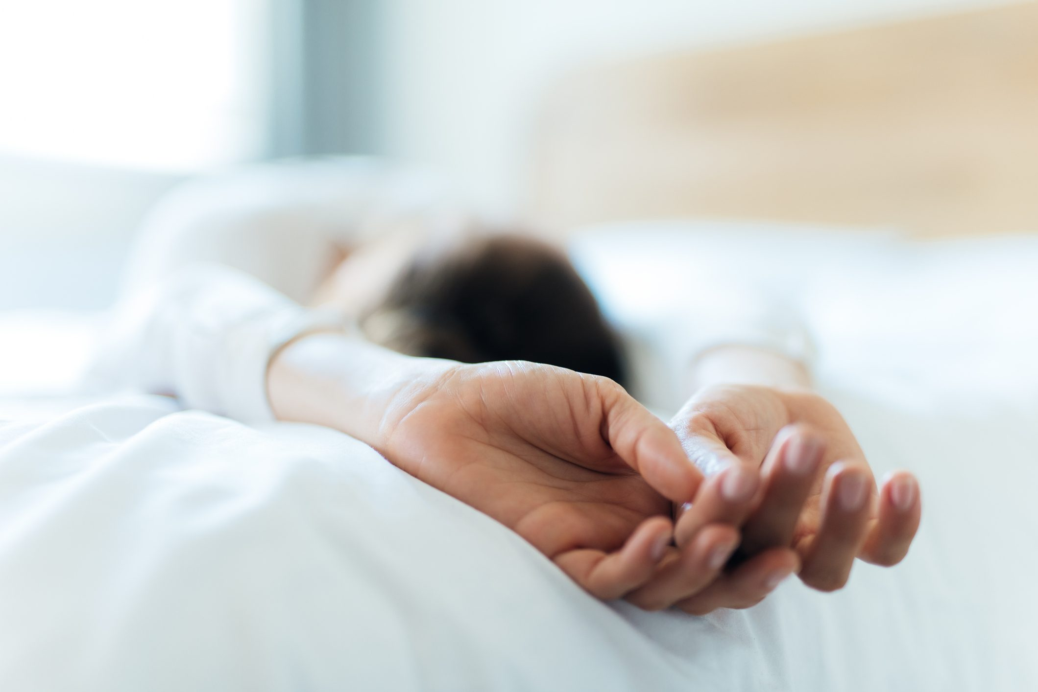 woman taking a nap on bed close up of hands