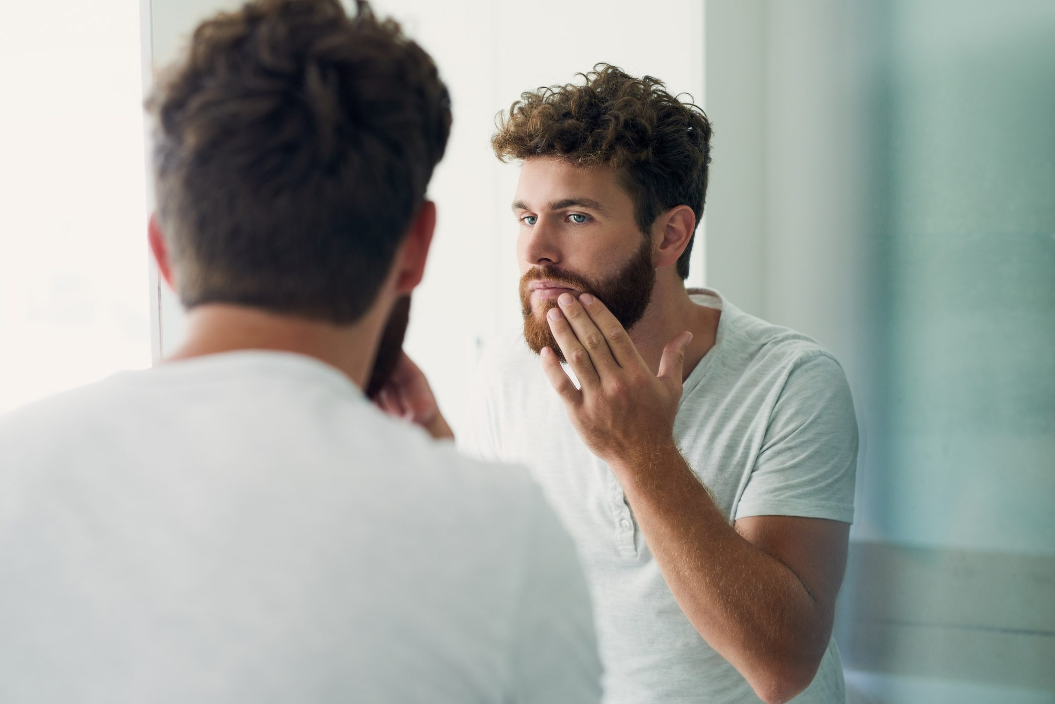 man looking at his beard in the mirror