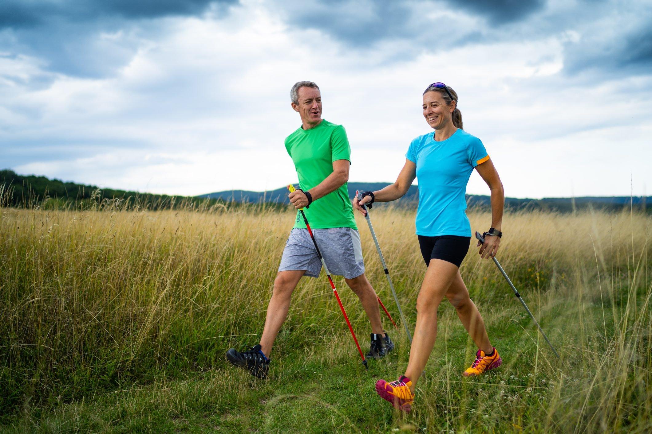 man and woman nordic walking