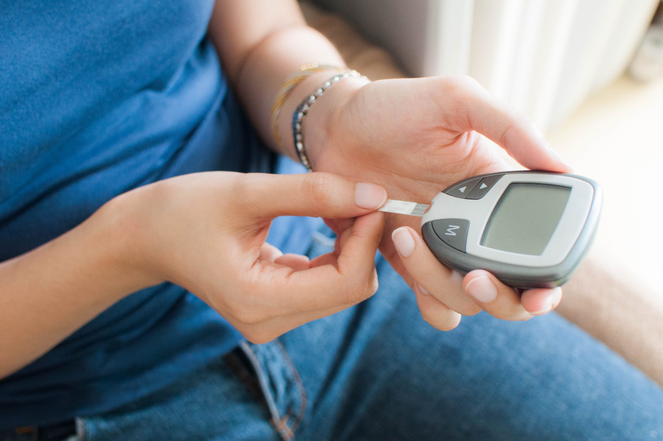 young woman using a glucometer for diabetes