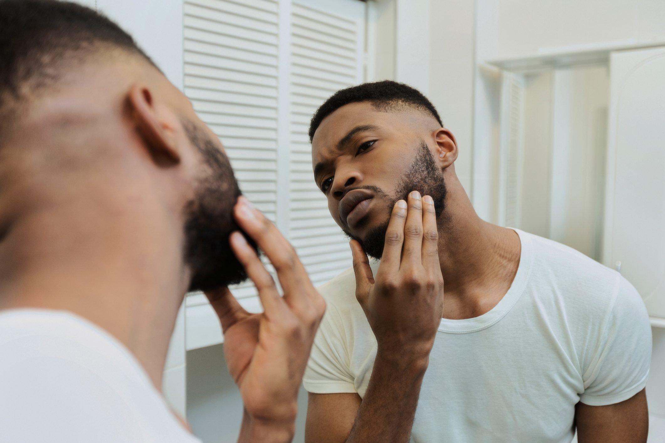 man inspecting beard in mirror