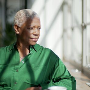 mature woman sitting at home looking out the window