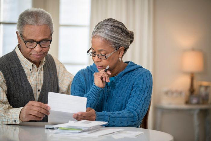 mature couple paying bills at home