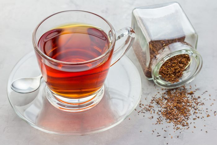 cup of healthy herbal rooibos red tea in glass cup and jar of dry tea