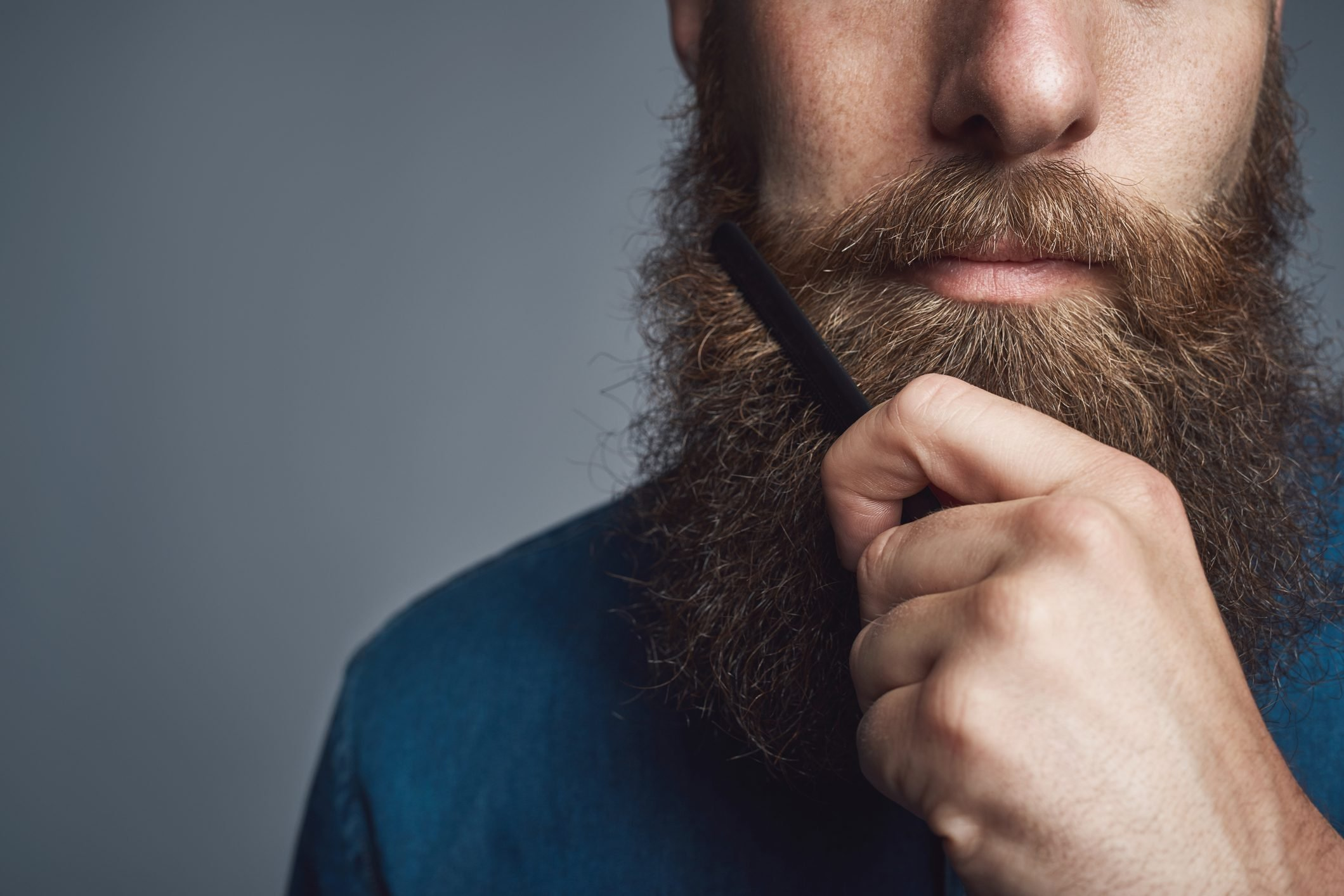 close up of young man brushing his beard